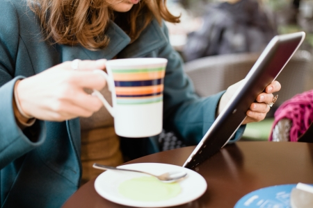 Woman using tablet computer in cafe drinking coffee Stock Photo - 23129872