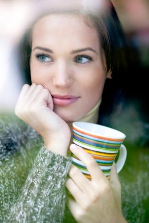 fenetres: Portrait d'une belle jeune femme avec une tasse de caf� de th� en regardant par la fen�tre en hiver faible profondeur de champ
