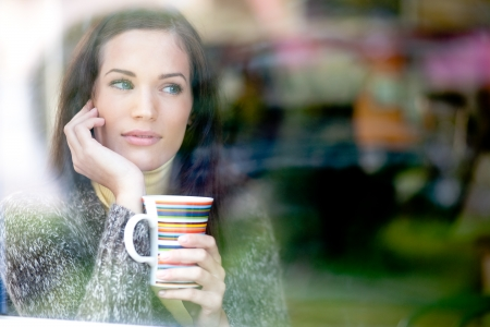 Winter portrait of a young woman looking out the window enjoying a hot cup of tea   coffee  Stock Photo