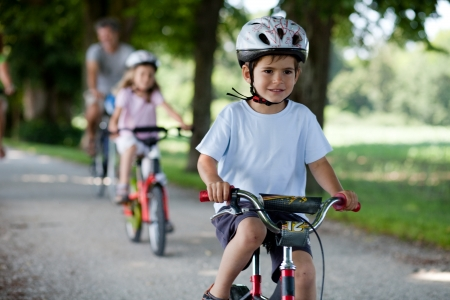 bike riding: 4-5 year old boy riding a bike in front of his family Stock Photo