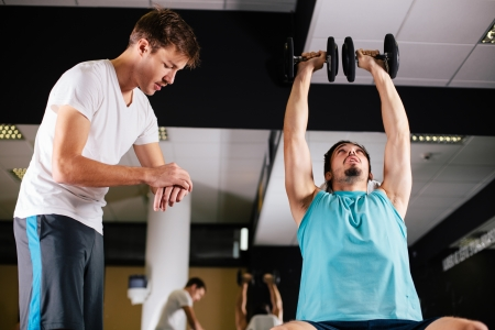 buddies: Gym buddies working out in gym timing exercise