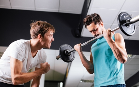 Young man motivating gym buddy during bicep exercise photo