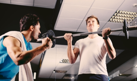fitness motivation: Young man motivating gym buddy during bicep exercise
