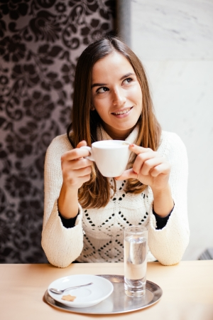Young woman drinking cofee in cafe photo