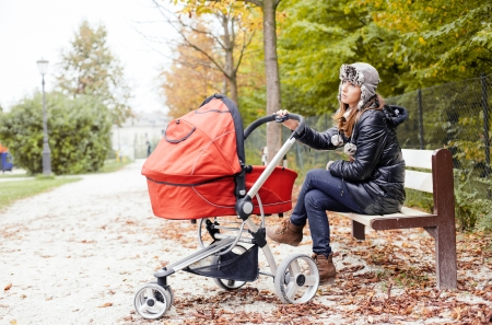 Tired mother sitting on park bench with baby in stroller photo
