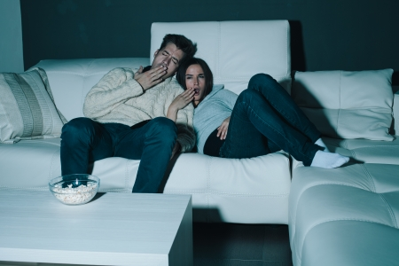Couple watching TV late at night yawning and falling asleep photo