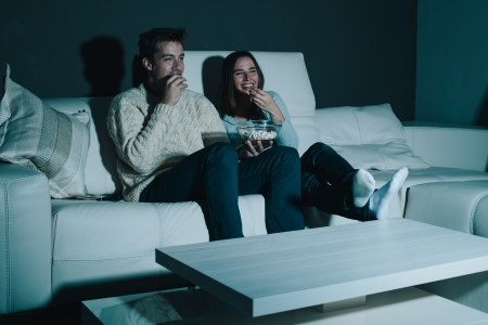 watching movie: Couple enjoying watching a movie at home laughing on the couch Stock Photo