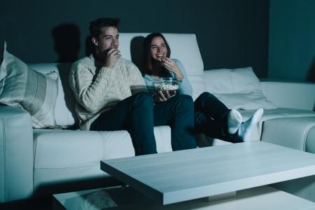family movies: Pareja disfrutando de ver una pel�cula en casa riendo en el sof�