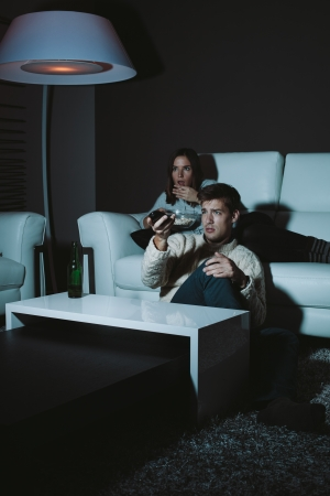 Young couple watching horror movie late at night photo