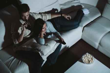 pareja viendo television: Joven pareja viendo televisión en casa por la noche
