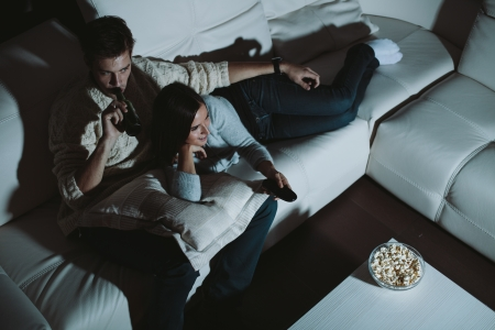 Young couple watching TV at home at night