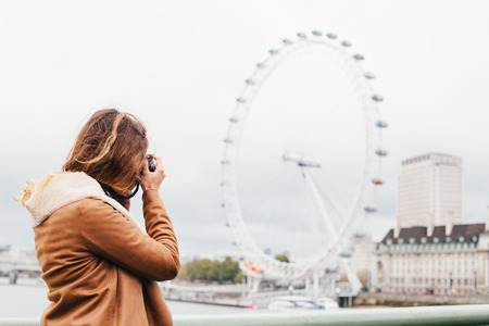 streets of london: Woman sightseeing and taking photos with DSLR camera