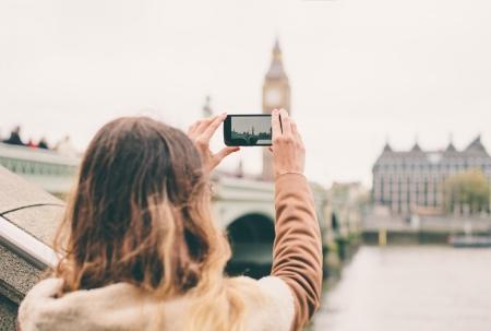 Jonge vrouw die een foto met haar telefoon in Londen