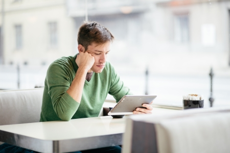 Young man using tablet computer in cafe Stock Photo - 24990508