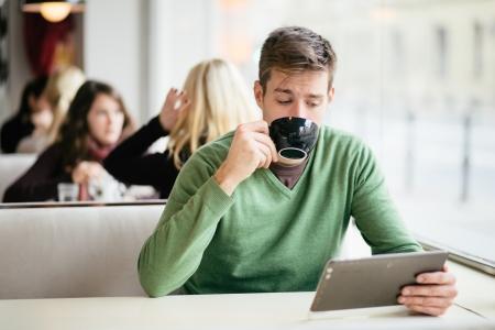 internet cafe: Hombre joven que bebe caf� en caf� y con tablet PC