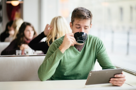 Young man drinking coffee in cafe and using tablet computer photo