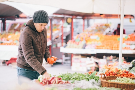 Man buying fresh vegetables at farmers market photo