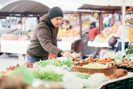 campesino: Hombre recogiendo verduras frescas en el mercado del agricultor