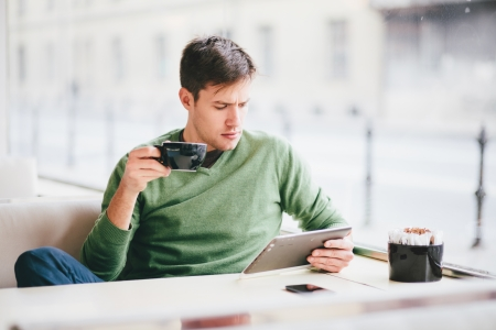 Young man using tablet computer in cafe photo