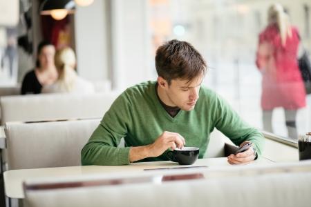 若い男がカフェでスマート フォンを使用して