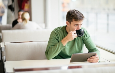 coffee shop: Young man drinking coffee in cafe and using tablet computer