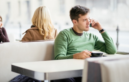 Young man talking on the phone in cafe Stock Photo