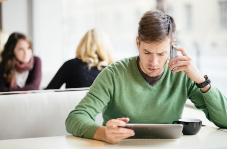 woman serious: Young man talking on the phone and using tablet computer