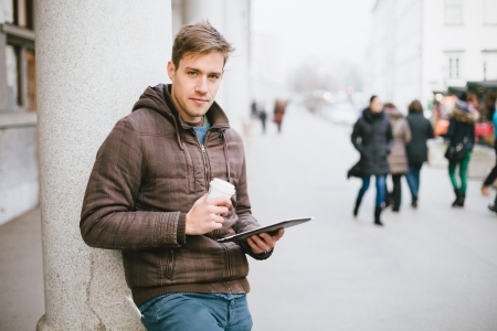 Young man drinking coffee on the street while using tablet computer photo