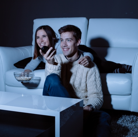 Young couple in love watching TV at night photo