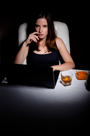Young woman using laptop drinking wiskey and smoking photo
