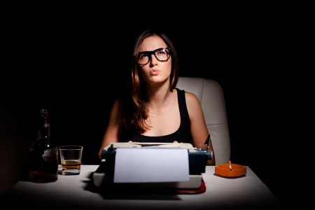write a letter: Young female novelist writing a book using typewriter