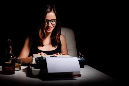 hombre escribiendo: El novelista escribiendo un libro sobre una máquina de escribir Foto de archivo