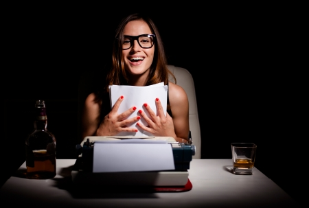 Young female novelist is happy because she finished writing her book Stock Photo