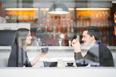 Couple in love drinking coffee laughing in cafe Stock Photo