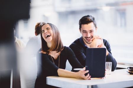 riendo: Joven pareja mirando las fotos en la computadora de la tableta de risa
