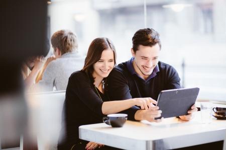 riendo: Pareja mirando las fotos en la computadora de la tableta de risa en el caf�