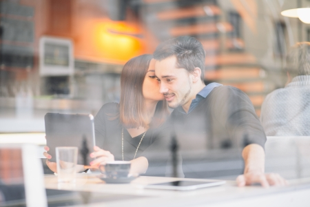 Young woman giving boyfriend kiss in coffee shop photo