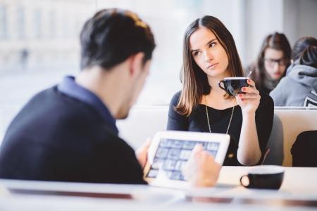 mujeres peleando: Mujer joven aburrido mientras el novio está con tablet PC en el café