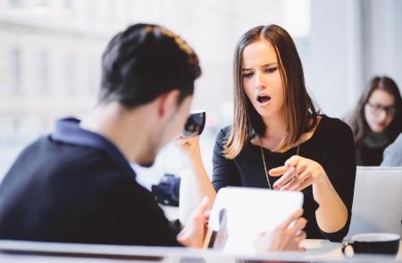pareja discutiendo: Mujer joven enojada con su novio novio está con tablet PC en el café
