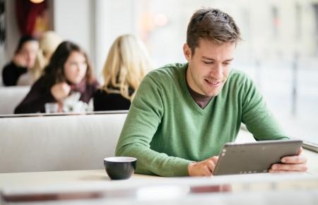 若い人の学生がカフェでタブレット コンピューターを使用して