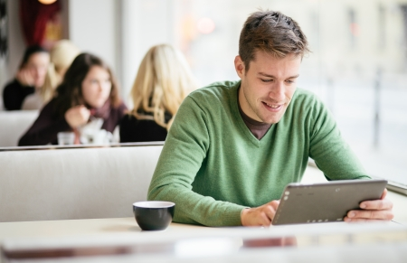 Young man   student using tablet computer in cafe photo