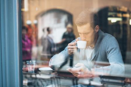 Mladý muž pití kávy v kavárně a pomocí počítače tablet