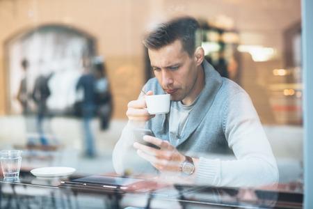 Hombre joven que bebe café en café y con tablet PC Foto de archivo - 27427768