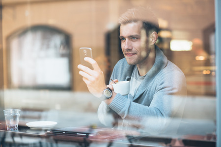 Young man taking a selfie in coffee shop photo