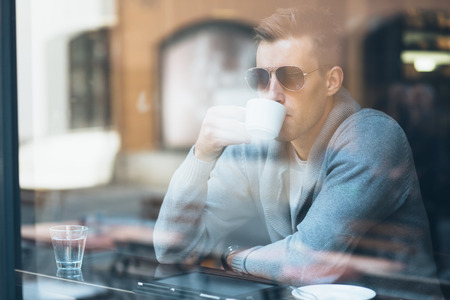 man looking out: Young man drinking coffee in cafe looking out the window Stock Photo