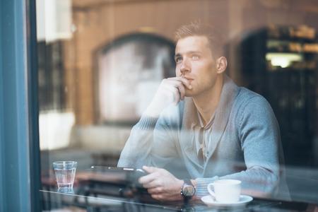 タブレット コンピューターを使用してコーヒー ショップで物思いに沈んだの若い男 写真素材