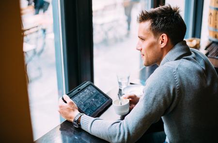 젊은 남자가 카페에서 커피를 마시고 태블릿 컴퓨터를 사용 하 스톡 콘텐츠