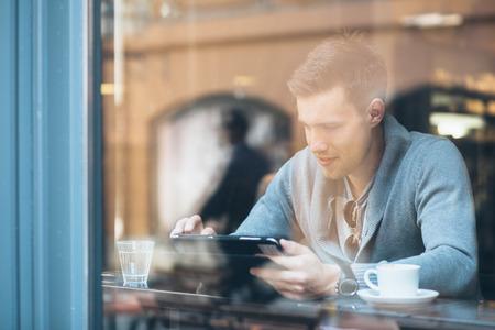 Mladý muž, pomocí počítače tablet v kavárně