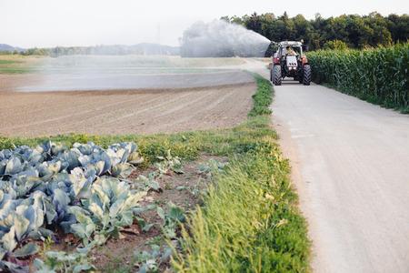 cisterna: Riego del granjero el campo utilizando el tractor y la cisterna