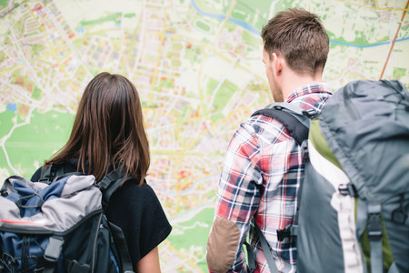 Couple of backpackers looking at city map photo